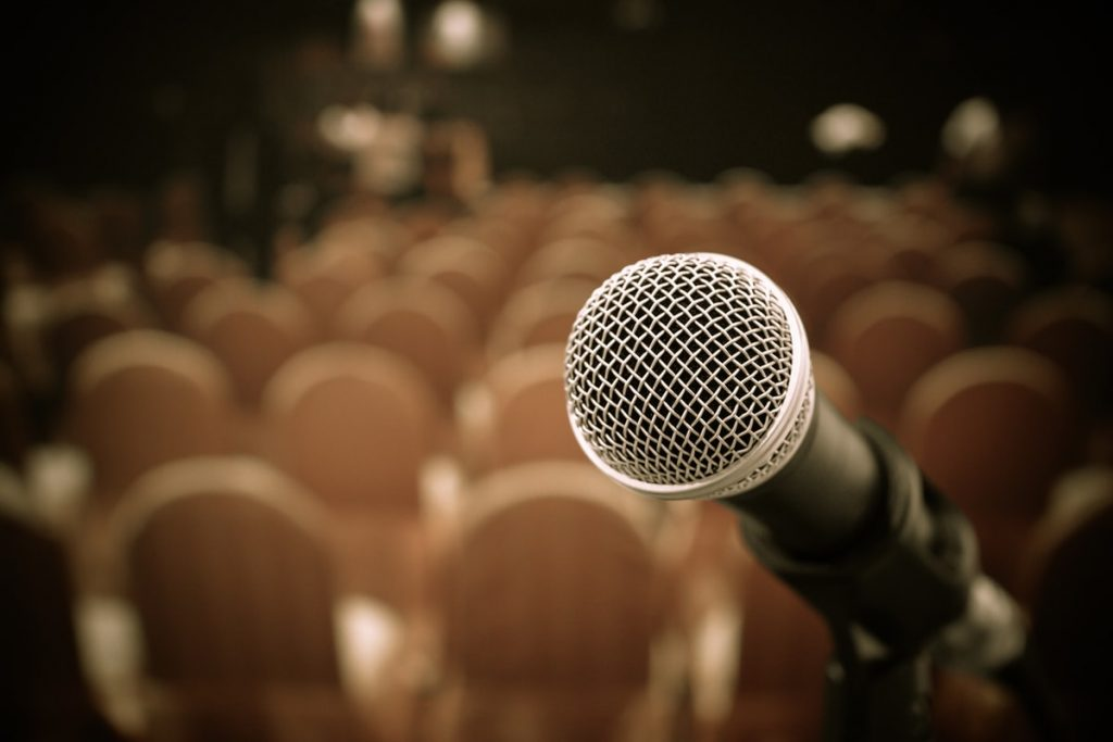 photo of a mic at an event before introducing funny speaker